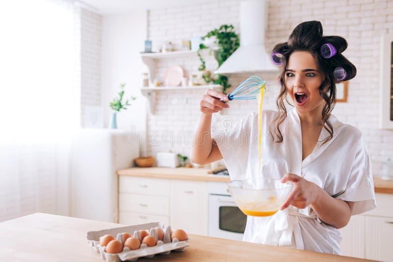 惊奇快乐的年轻女人看看她混和的黄色鸡蛋 立场在厨房和奇迹里 在容器的鸡蛋在桌上 免版税库存图片