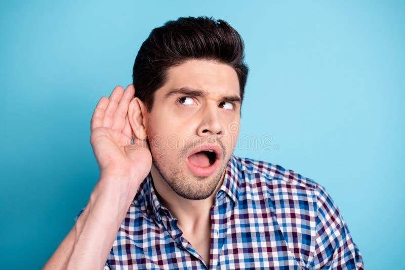 惊奇接近的照片他他他的强壮男子在耳朵神色附近听谣言喋喋不休者人展示大兴趣手臂间的棕榈 免版税库存图片