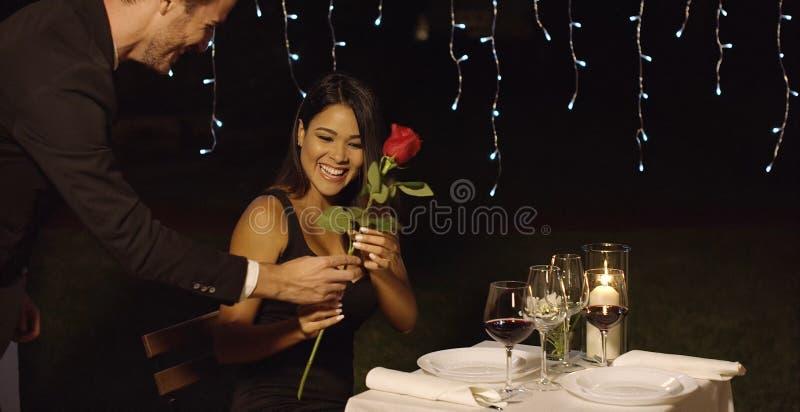 惊奇浪漫的人他的与玫瑰的日期 免版税图库摄影