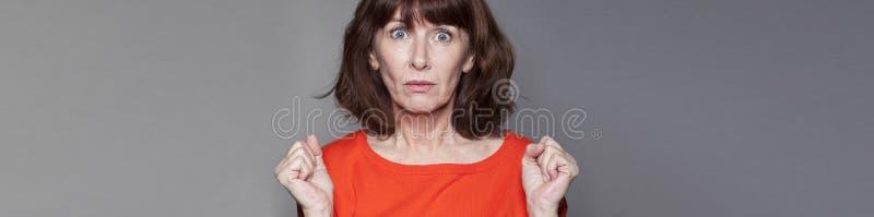 惊奇的中部变老了表达的妇女误解,灰色横幅 免版税库存照片