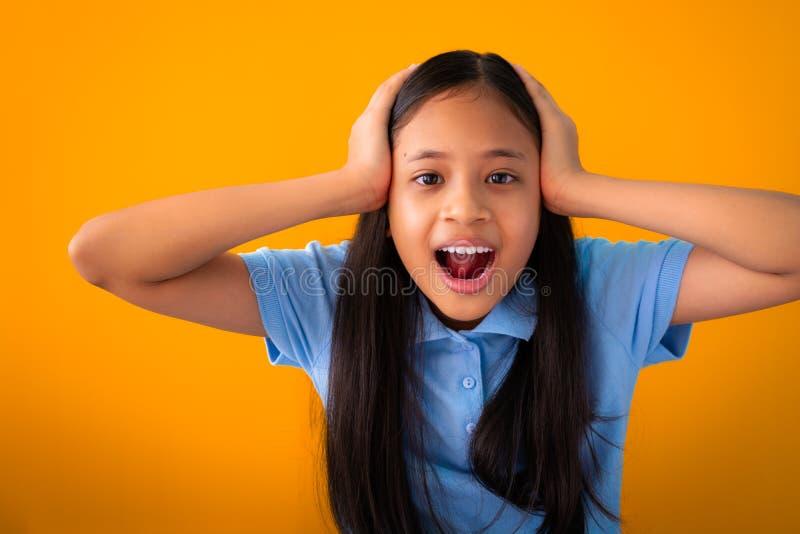 惊奇的俏丽的女孩被隔绝的橙色背景特写镜头画象  免版税库存图片