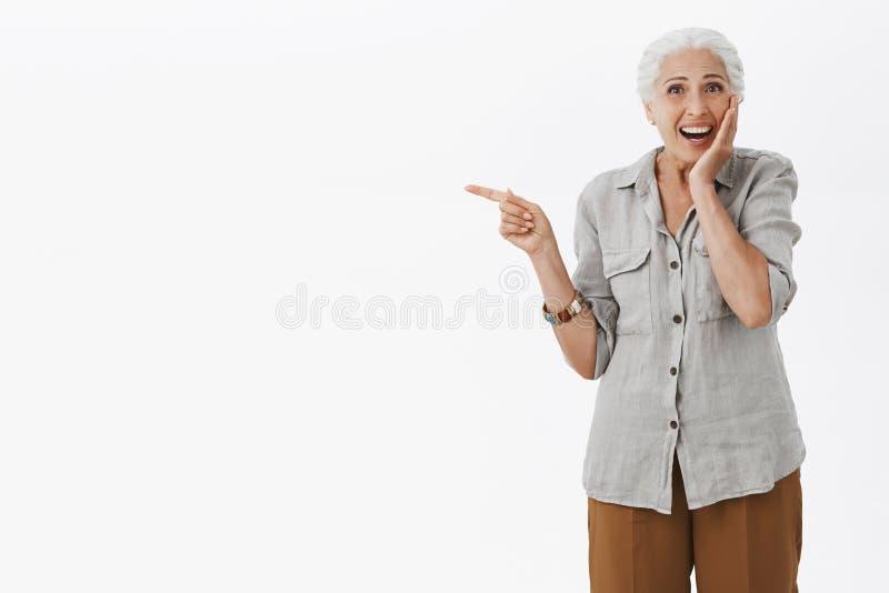 惊奇的和高兴惊奇逗人喜爱的老婆婆画象轻轻地接触面颊的偶然衬衣的从兴奋微笑 免版税图库摄影