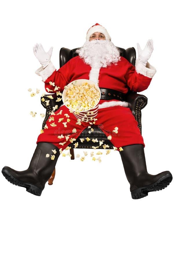 惊奇的圣诞老人在椅子和玉米花飞行坐 图库摄影
