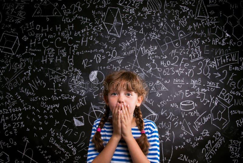 惊奇的女孩,在嘴,有数学sym的黑板的手 免版税图库摄影