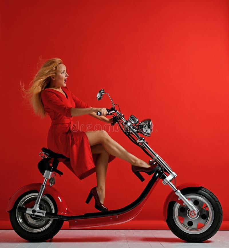 惊奇的妇女乘驾新的电车摩托车自行车滑行车自行车红色礼服 免版税库存照片