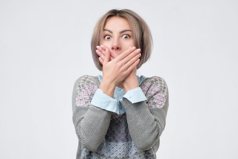 惊奇的妇女覆盖物嘴用手和凝视照相机 免版税图库摄影