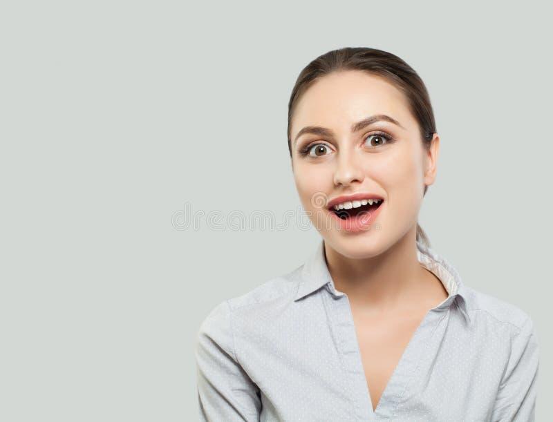 惊奇的妇女 在白色背景的年轻女性面孔 免版税库存照片