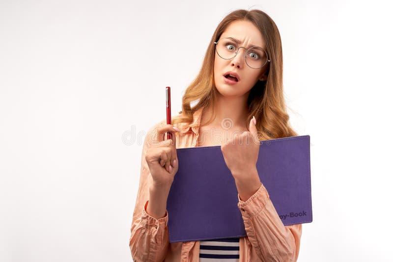 惊奇的学生妇女拿着课本,惊吓了表情,在通过高考前的忧虑 免版税库存图片