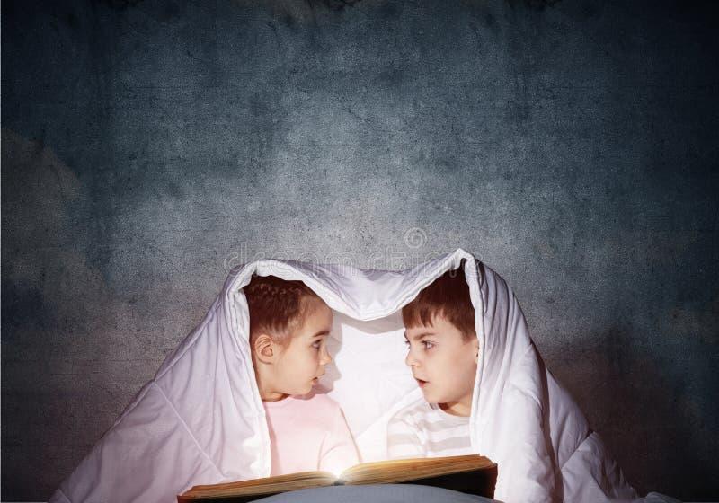 惊奇的孩子在床上的读可怕故事 免版税库存图片