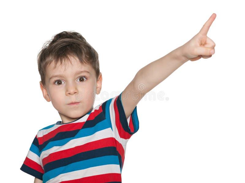 惊奇的小男孩显示他的手指在旁边 免版税库存图片