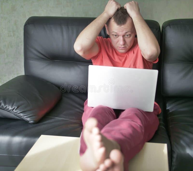 惊奇的年轻人坐有一台膝上型计算机的沙发在他的客厅 免版税库存照片