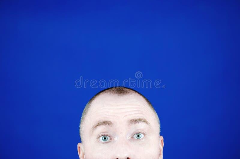 惊奇的年轻人的眼睛 害怕嫉妒 偷看从框架和拷贝空间的底部的头 库存图片