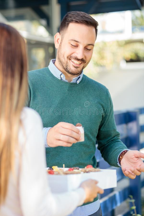 惊奇的年轻女人她的丈夫或男朋友有礼物盒的甜点 免版税图库摄影