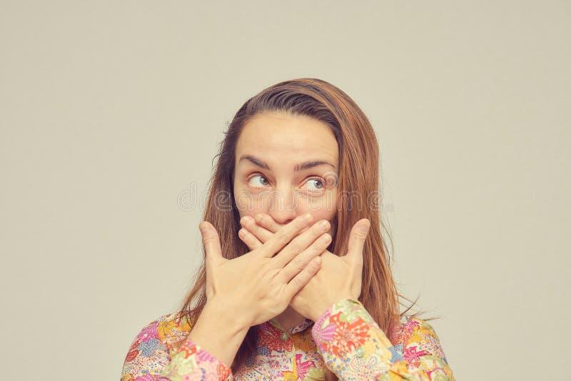 惊奇的年轻女人用她的手在白色背景盖她的嘴,站立 看对边的眼睛 俄国女孩 免版税图库摄影
