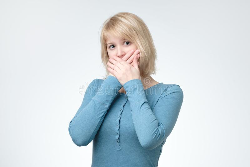 惊奇的年轻女人覆盖物嘴用手 免版税库存图片