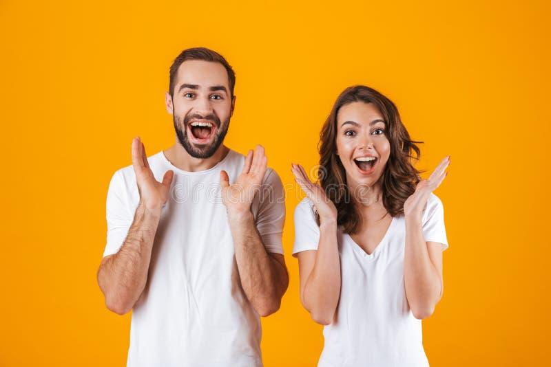 惊奇的微笑人男人和的妇女画象基本的衣物的,当站立一起隔绝在黄色背景时 库存图片