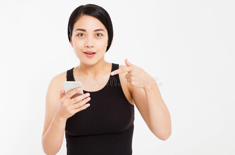 惊奇的情感亚洲女孩举行在白色背景隔绝的电话和针对性的手 库存图片