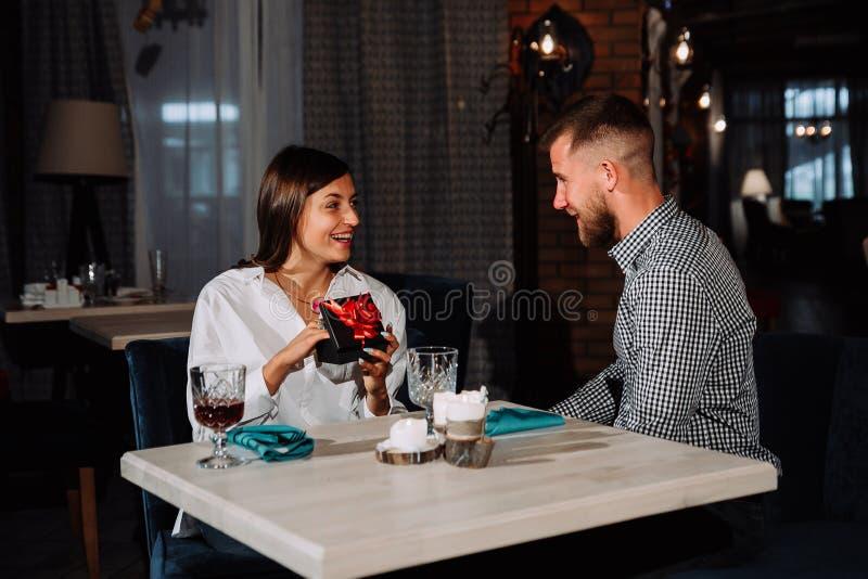 惊奇的愉快的妇女由桌坐在咖啡馆的日期和得到礼物 免版税图库摄影