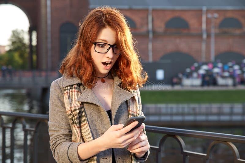 惊奇的愉快的红头发人妇女在镜片和秋天给r穿衣 免版税图库摄影