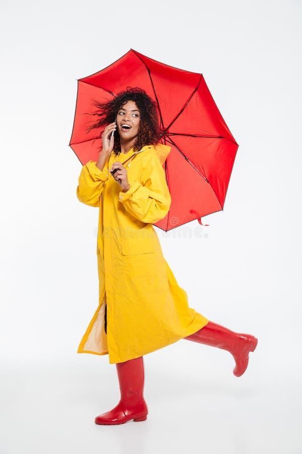惊奇的愉快的非洲妇女的全长图象雨衣的 库存图片