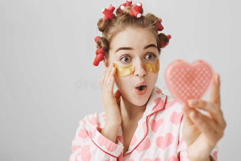 惊奇的或被打动的女孩特写镜头画象头发卷发的人的和眼睛修补看心形的镜子的面具 库存照片