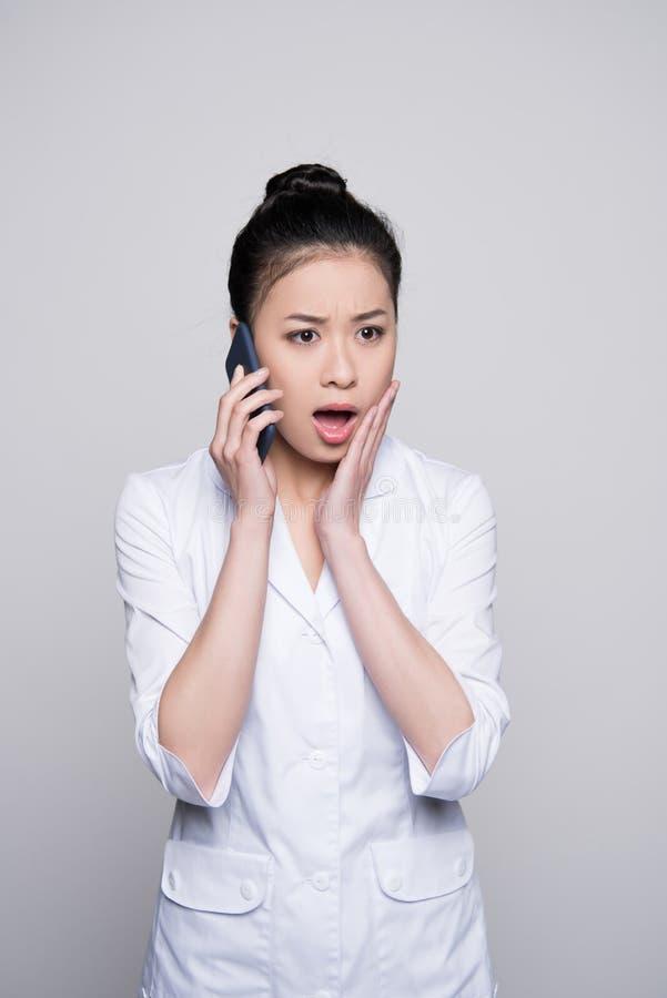 惊奇的护士谈话在电话 库存图片