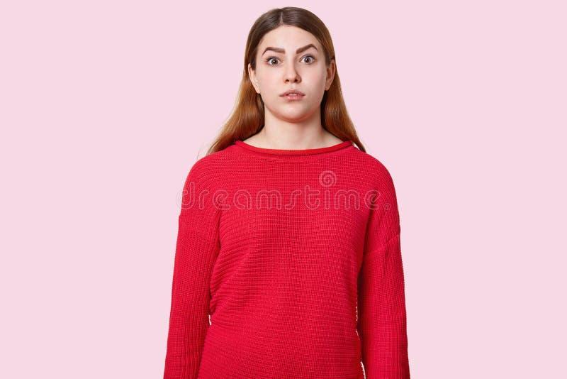 惊奇的欧洲妇女射击的腰部有长的直发的,在吃惊抬眼眉,穿戴在红色套头衫,起反应 库存图片