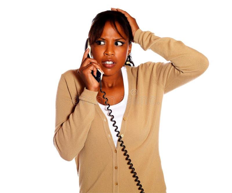 惊奇的沉思妇女说在电话里 库存照片