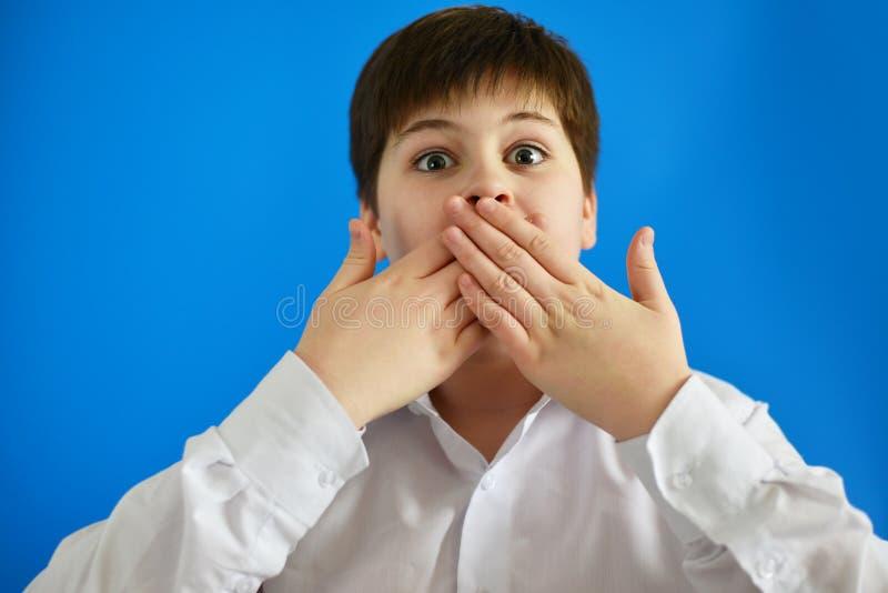 惊奇的男孩关闭嘴用手 图库摄影