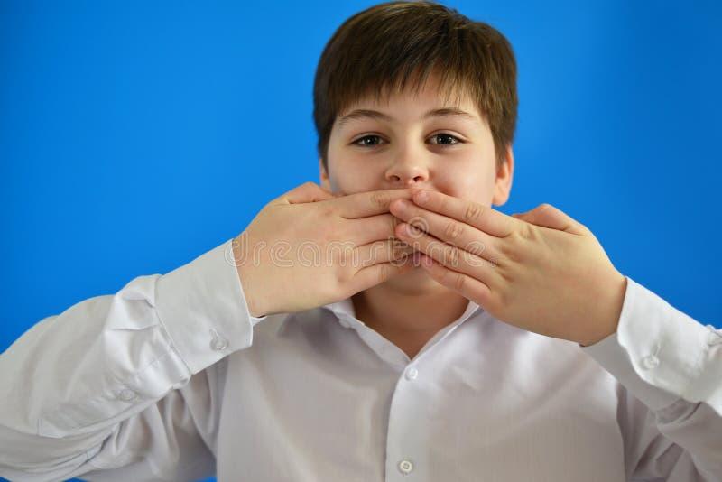 惊奇的男孩关闭嘴用手 免版税库存照片