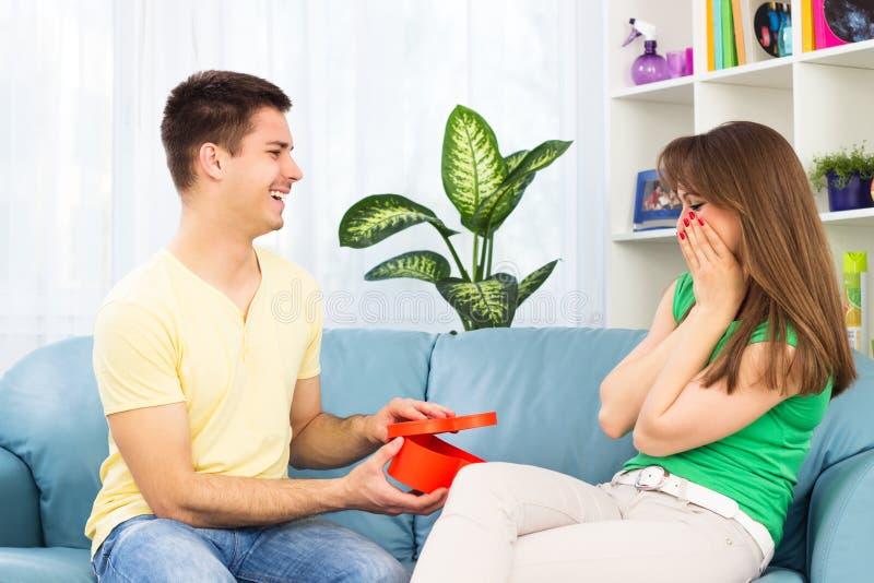 惊奇的男朋友他的有礼物的女朋友 免版税库存图片