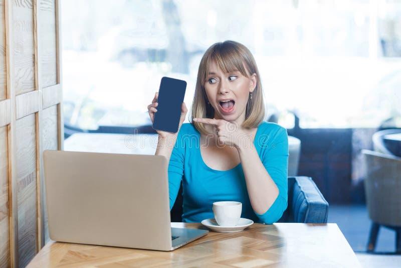 惊奇的美丽的年轻白肤金发的妇女画象蓝色T恤杉的,坐与膝上型计算机,拿着和指向流动显示和 免版税库存图片