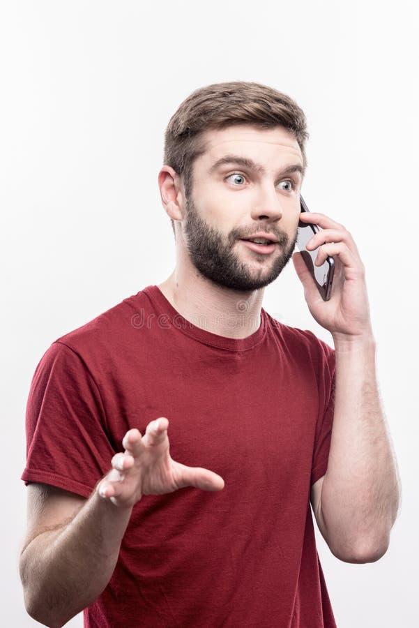 惊奇的蓝眼睛的商人感觉,当告诉他的商务伙伴时 免版税库存图片