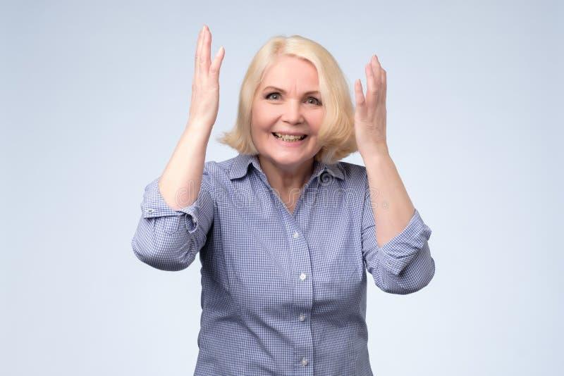 惊奇的资深白肤金发的妇女用惊奇或冲击的手由意外消息 库存图片