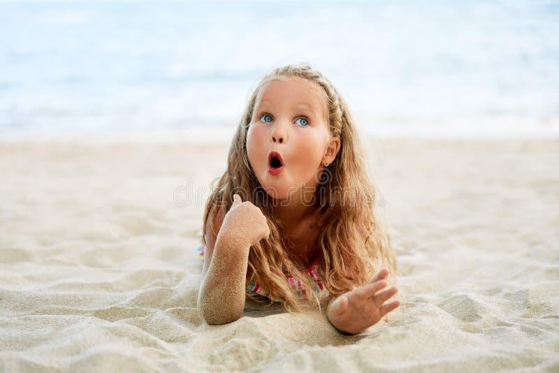 惊奇的逗人喜爱的矮小的白肤金发的女孩放松在海滩在度假夏天休假 库存照片