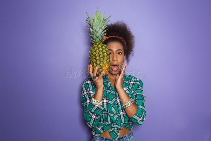 惊奇的非裔美国人的妇女用在颜色背景的菠萝 免版税库存照片
