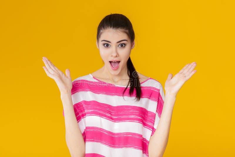 色情p导航_惊奇的年轻深色的妇女画象桃红色衬衣的在黄色背景 女孩看照相机