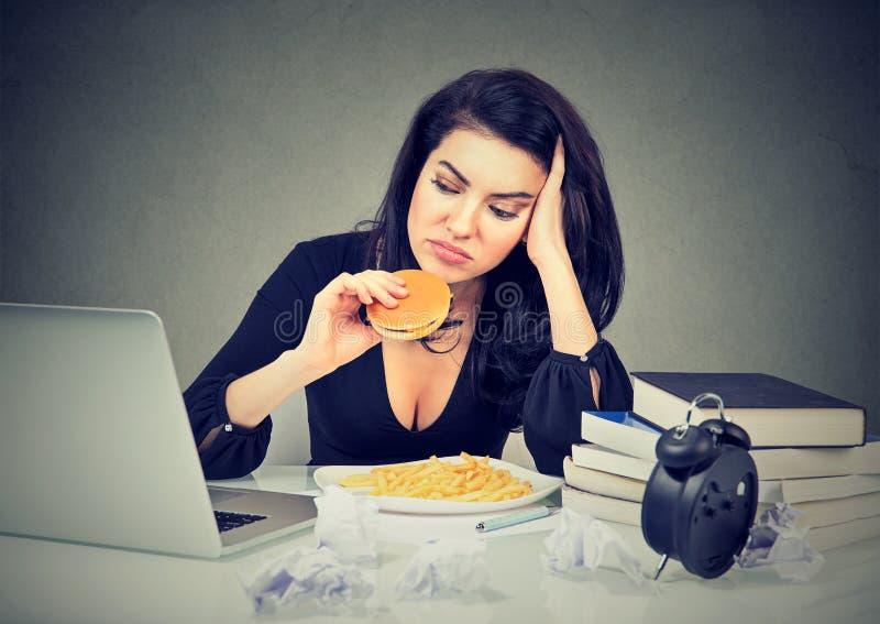 惯座生活方式和速食概念 坐在书桌的被注重的妇女吃汉堡包 库存图片