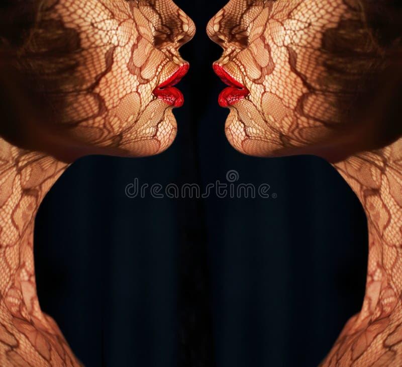 幻想。与网眼图案的两张妇女的面孔在彼此对面。反射 免版税库存图片