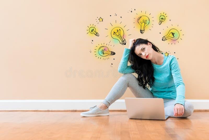 想法与使用膝上型计算机的妇女的电灯泡 图库摄影
