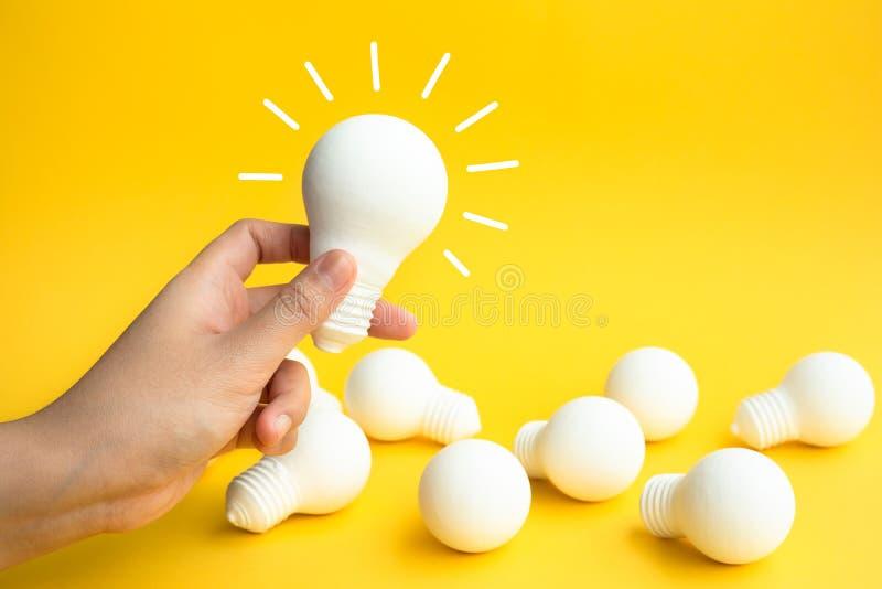 想法与女性手藏品电灯泡的启发概念在淡色背景 免版税图库摄影