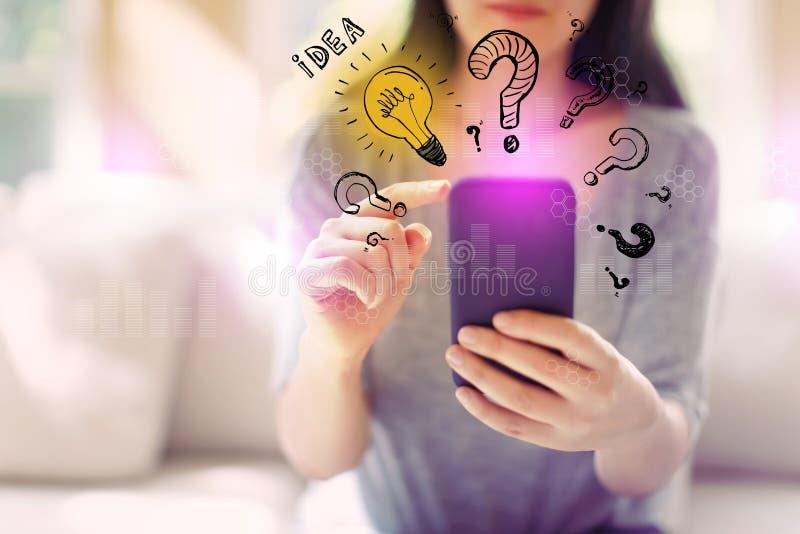 想法与问号的电灯泡与使用智能手机的妇女 免版税库存图片