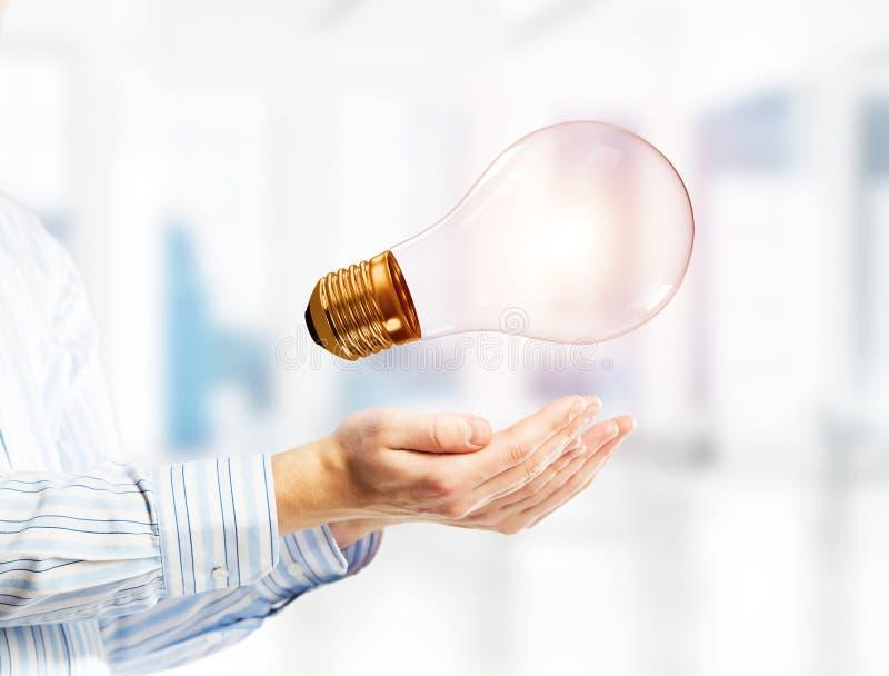 想法或能量的概念作为电灯泡在男性棕榈 混合画法 库存照片
