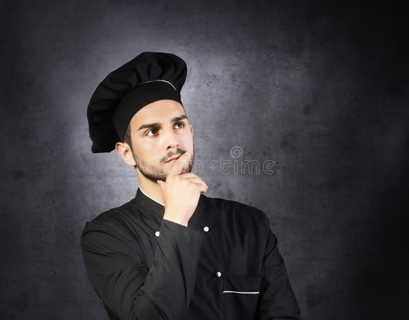 想法的厨师烹饪器材的画象在黑制服的 免版税图库摄影