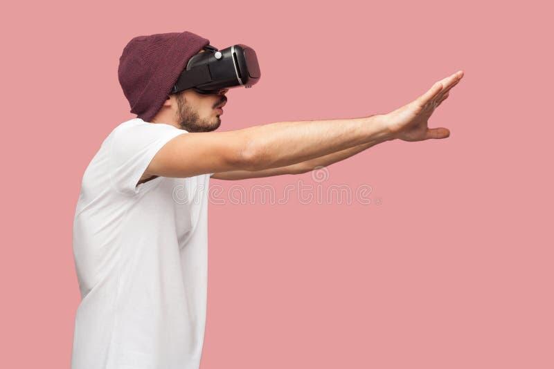 想知道白色衬衫和偶然帽子身分的,打电子游戏的佩带的vr有胡子的年轻行家人画象侧视图  库存照片