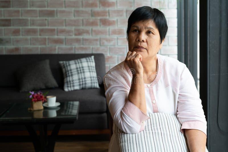 想知道资深亚洲的妇女认为和看斜向一边,认为和 免版税库存图片