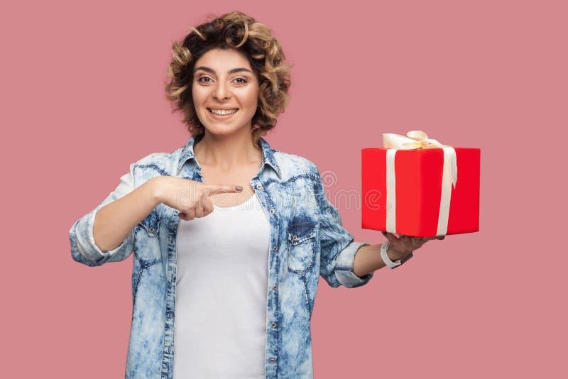 想要您?愉快的年轻女人画象蓝色衬衣的有拿着红色礼物盒和指向手指的curlty发型的,看 免版税库存照片