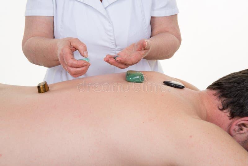 愈疗者使用水晶疏导她的患者的能源中心 库存照片