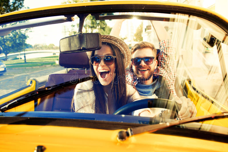 愉快一起旅行 微笑快乐的年轻的夫妇,当乘坐在onvertible时 库存图片