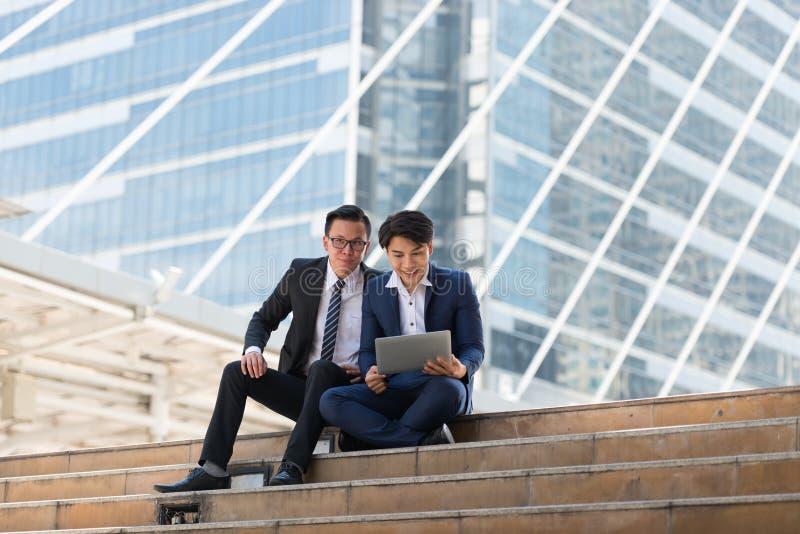 愉快亚洲人两的商人,当选址看见膝上型计算机时 在busi 图库摄影